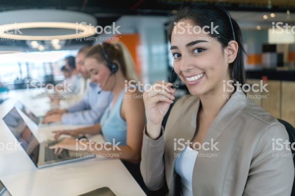 Portrait of a happy woman working at a call center looking at the camera smiling and wearing a headset